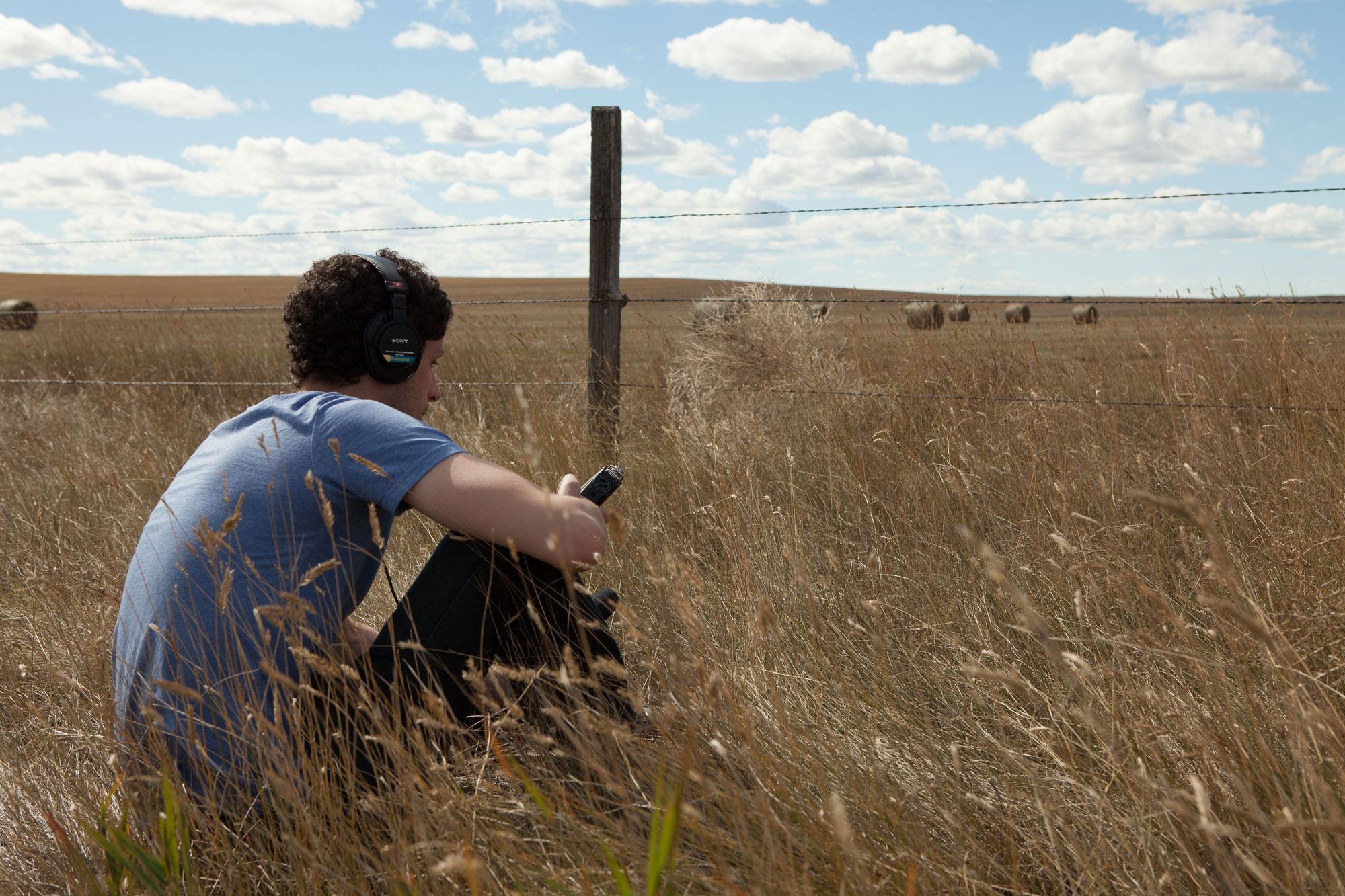 Tarek sits near a barbed wire fence outside Richey, Mont., capturing the sounds of the prairie.